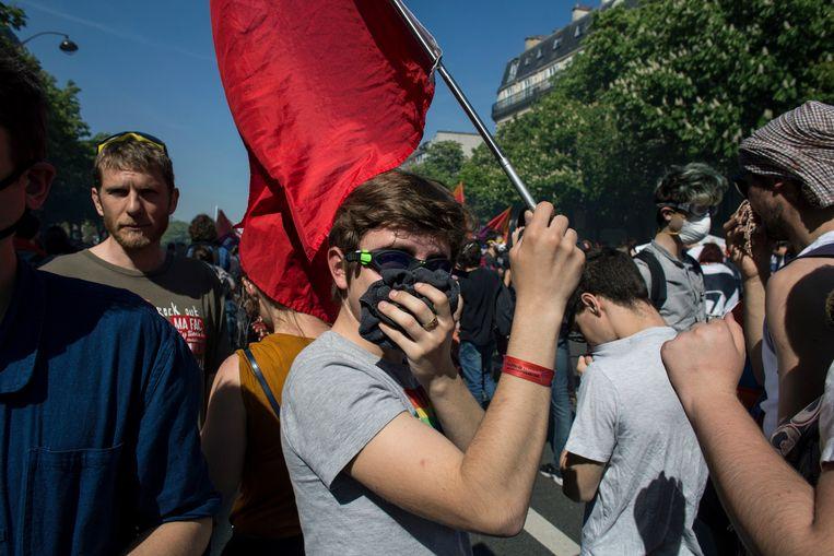 Een demonstrant beschermt zich tegen traangas van de politie op 19 april 2018 in Parijs.  Beeld Bart Koetsier