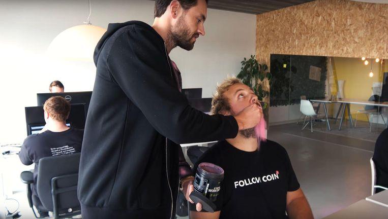 Fitnessgoeroe Joel Beukers geeft een cursist een paars goedje dat uit zijn mond valt. Beeld RV
