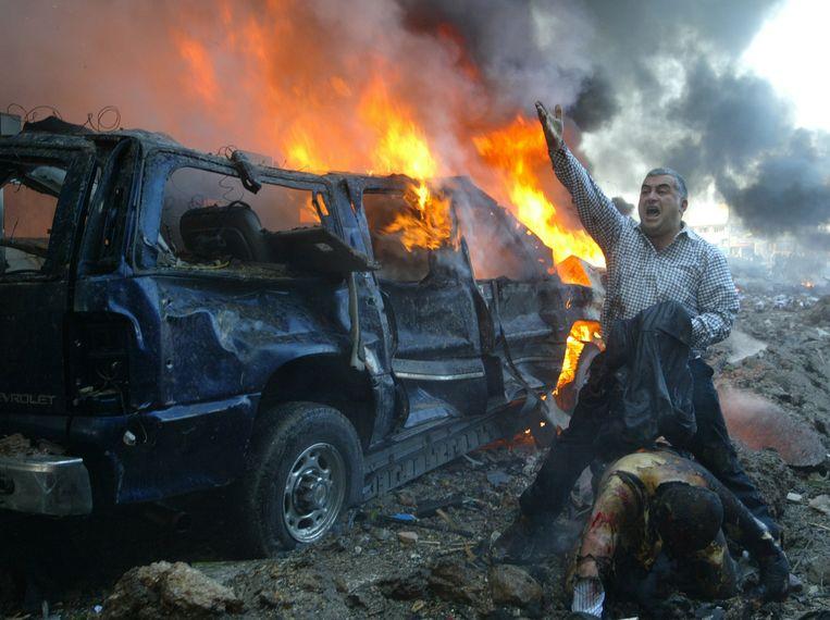 Een Libanese man roept om hulp voor een gewonde vlak bij de plek waar de autobom is ontploft waarbij Hariri omkwam.  Beeld Reuters