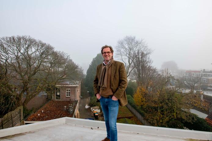 Yannick van Lith op het plat dak van het pand aan het Wilhelminapark dat hij laat verbouwen. Achter hem de diepe tuinen die een nieuw dwaalgebied mogelijk maken.