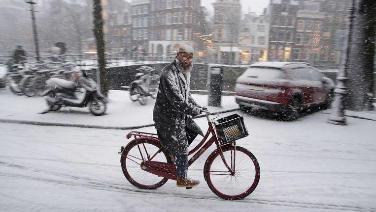 Een man trotseert al fietsend de sneeuw. Beeld anp