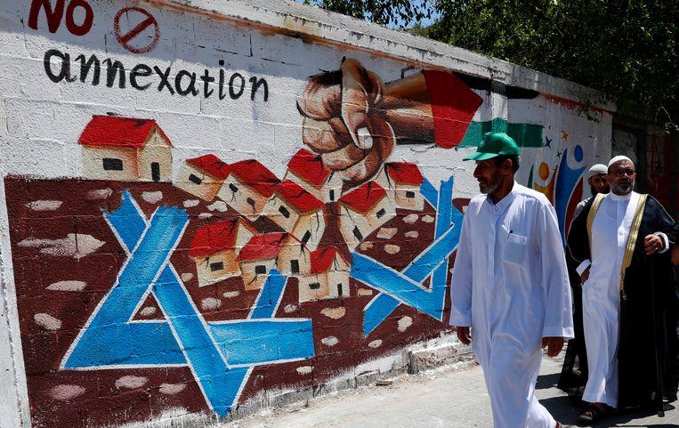 Hamas-aanhangers lopen langs een muurschildering die zich uitspreekt tegen Israëls annexatieplannen van de  Westelijke Jordaanoever.