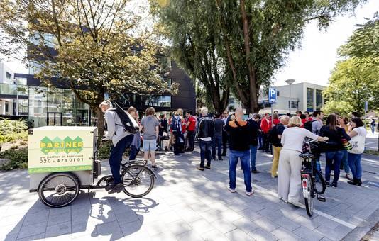 Medewerkers van maaltijdbezorger Deliveroo verzamelen zich voor de rechtbank in Amsterdam.