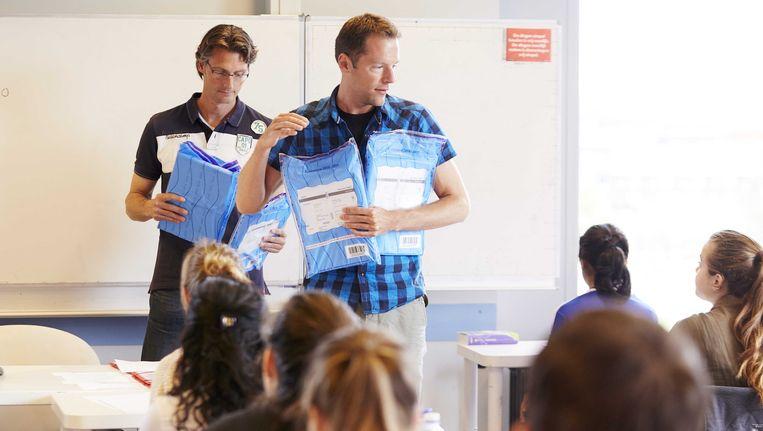 Eer leerkracht deelt eindexamens uit. Beeld ANP