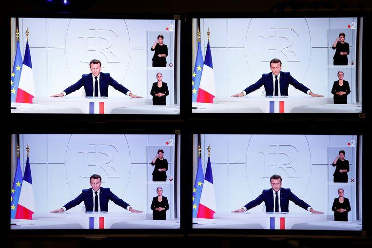 Macron tijdens zijn toespraak op televisieschermen in Parijs.  Beeld REUTERS