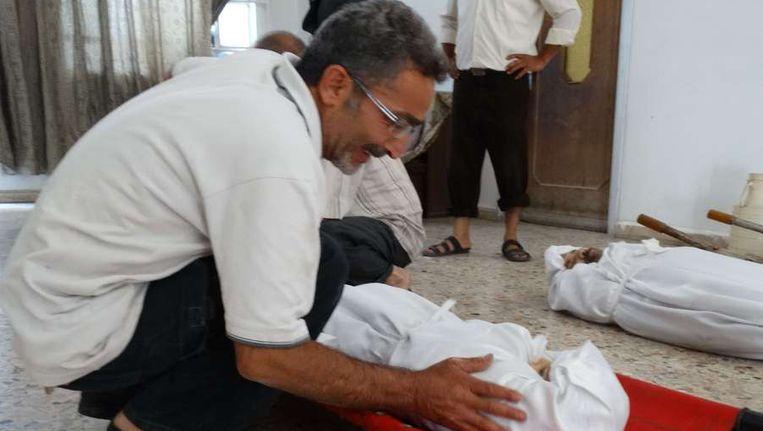 Een foto, vrijgegeven door de Syrische oppositie, van een man die rouwt om een familielid. Beeld afp