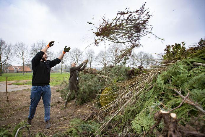 Ingrid Leferink en zoon Bas gooien de restanten van de heg op de stapel van het paasvuur.
