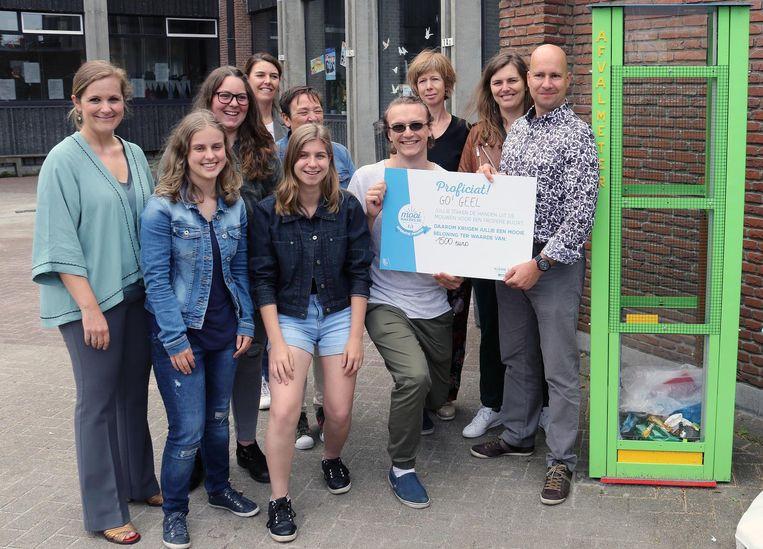 Enkele leerlingen en leerkrachten tonen hun cheque voor 1.500 euro bij de zwerfvuilmeter.