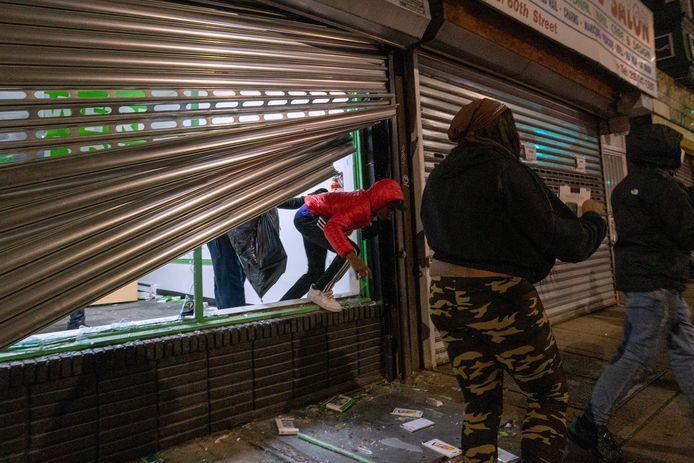 Plunderaars bij een opengebroken winkel in Philadelphia.