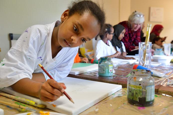 KInderen van statushouders aan het schilderen, een initiatief van kunstenares Maaike Vermeulen (achteraan) om ze afleiding van hun sores te bieden.