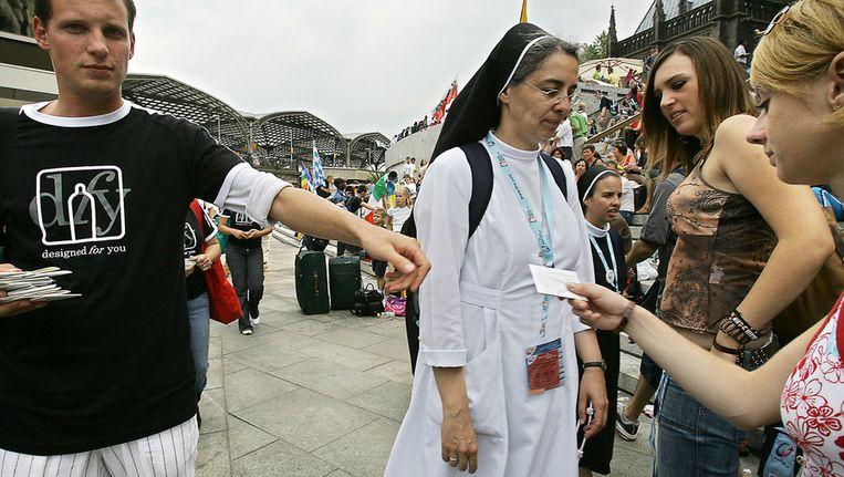 Een non krijgt tijdens de Wereldjongerendagen van 2005 in Keulen een condoom aangeboden. Beeld AFP