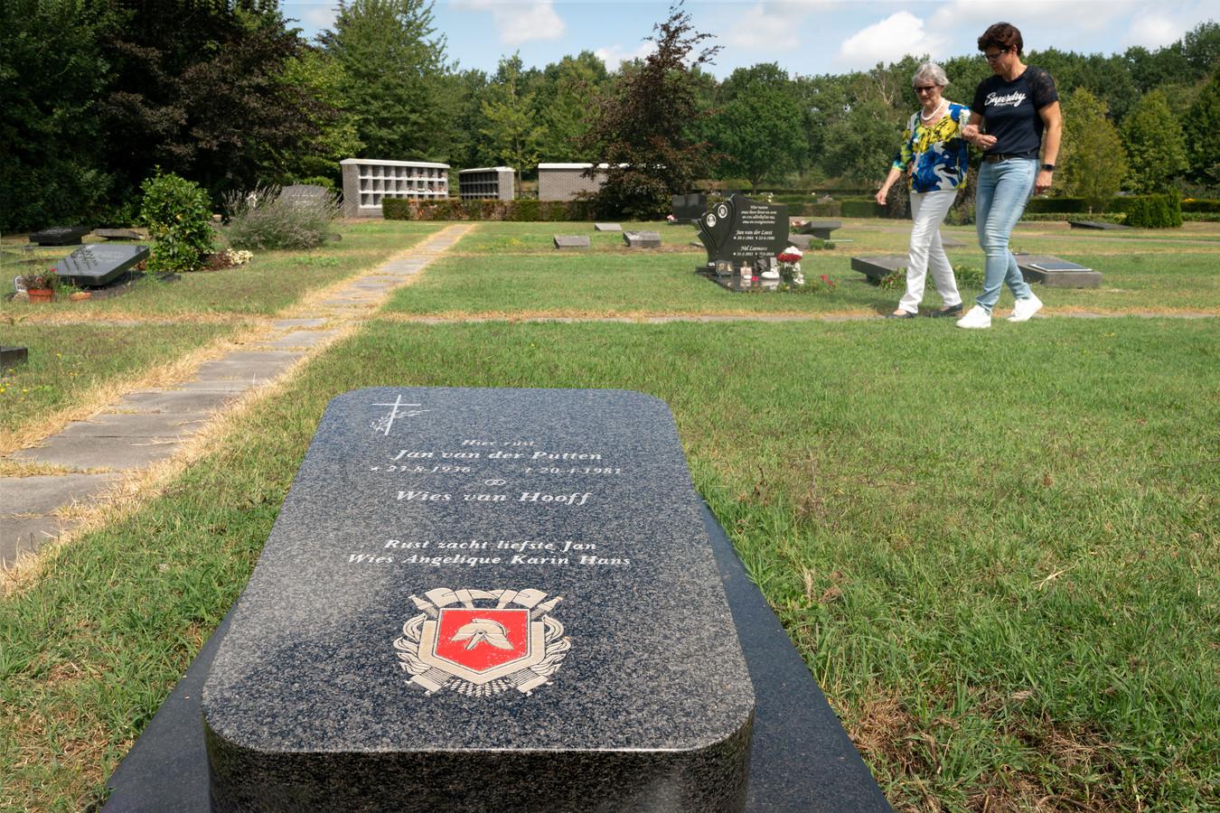 Wies van der Putten loopt richting het graf van haar man Jan van der Putten. Dochter Karin Biekens loopt met haar mee.