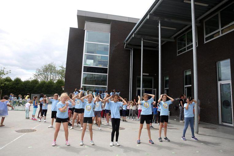 De leerlingen van Den Top dansen voor hun huidige schoolgebouw, dat nog maar enkele jaren in gebruik is.