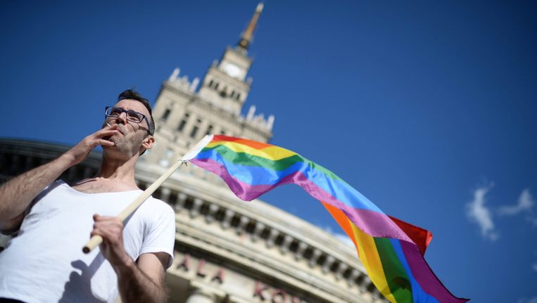 Een deelnemer aan de jaarlijkse Gay Pride Parade in Warschau zwaait met een regenboogvlag Beeld epa