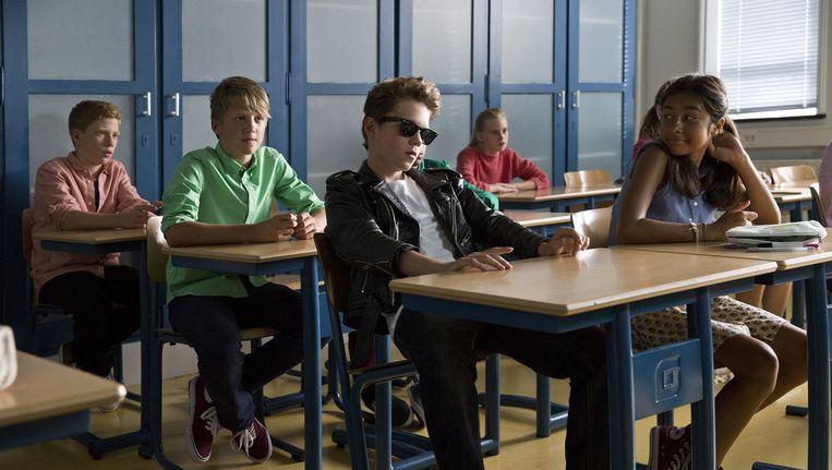 Rikkie - met vetkuif, leren jasje en zonnebril - in zijn nieuwe klas. Beeld Ray van der Bas