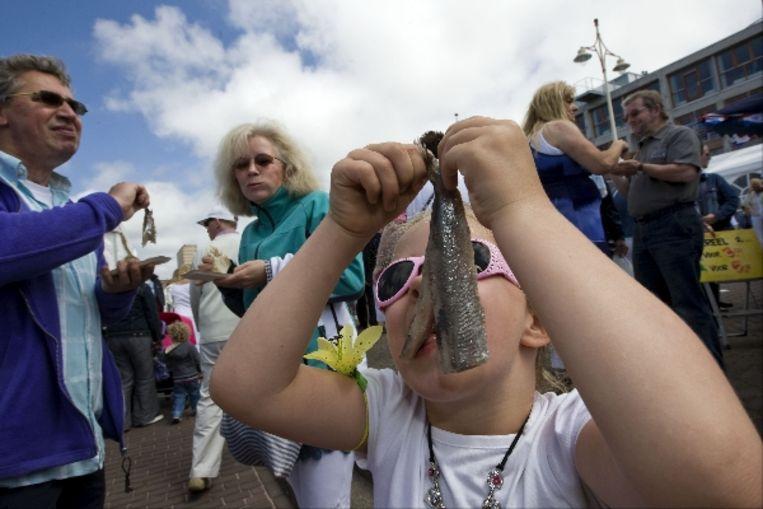 Een jonge bezoekster van vlaggetjesdag schuift een haring naar binnen op de boulevard van Scheveningen. Vlaggetjesdag is de traditionele feestelijke opening van het haringseizoen in de Zuid-Hollandse badplaats. ( ANP) Beeld ANP