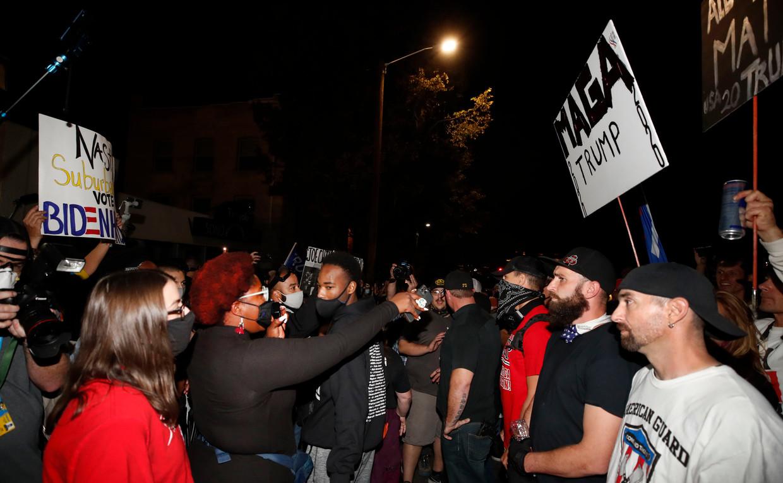 Black Lives Matter-manifestanten (links) staan tegenover extreemrechtse Proud Boys tijdens het debat van Mike Pence en Kamala Harris in Salt Lake City. Beeld AFP