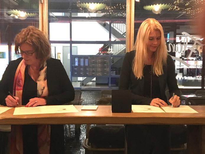 Veronique Holtmaat (Stichting Jong) en wethouder Marijo Immink ondertekenen het aanbestedingscontract.