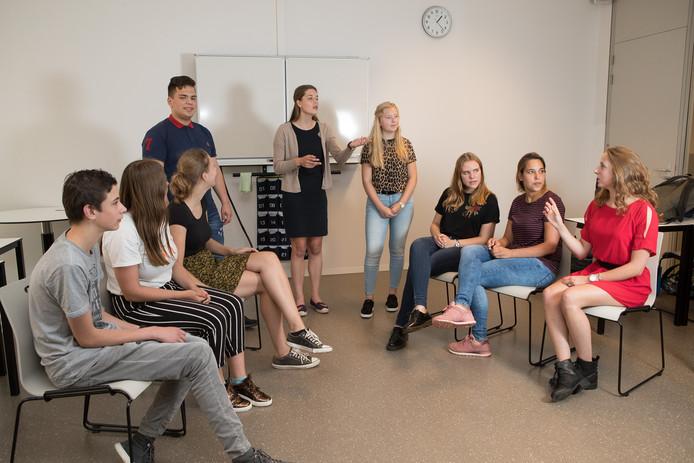 De leden van de debatclub oefenen. Vlnr Justin, Elke, Josee, Simon, Britt, Willemijn, Nienke, Joyce en Renske.