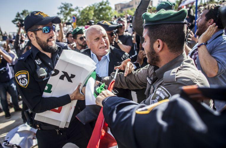 Een agent trekt een protestbord uit de handen van een Palestijnse betoger. Beeld AP