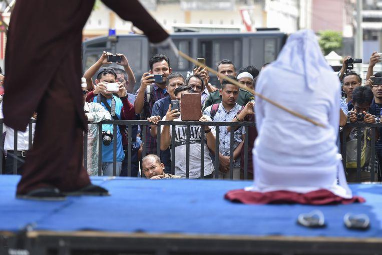 Een Indonesische vrouw die stokslagen krijgt. Beeld AFP
