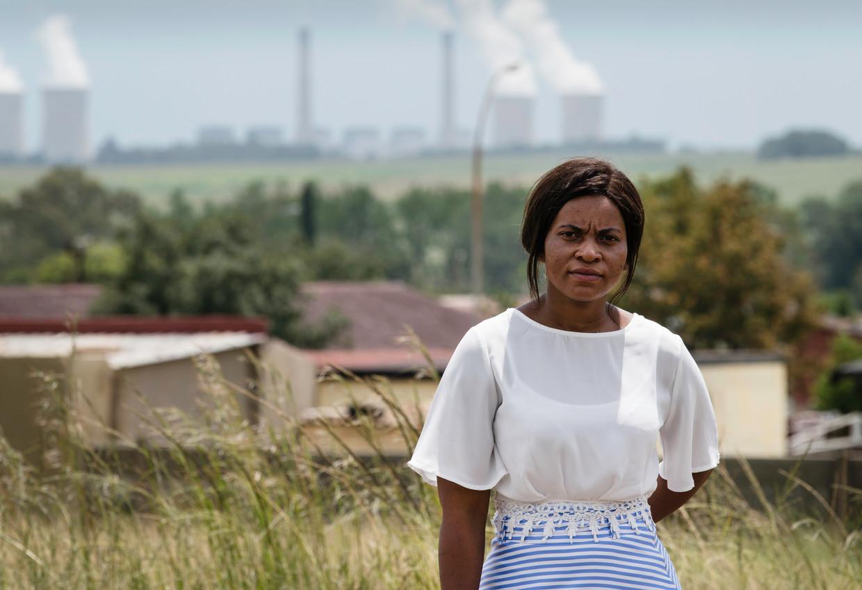 Gezondheidswerkster Isabella Nkareng, met achter haar een van de twee enorme kolencentrales. De lucht in Kriel kent de op een na hoogste concentratie zwaveldioxide en de hoogste concentratie stikstofdioxide ter wereld.