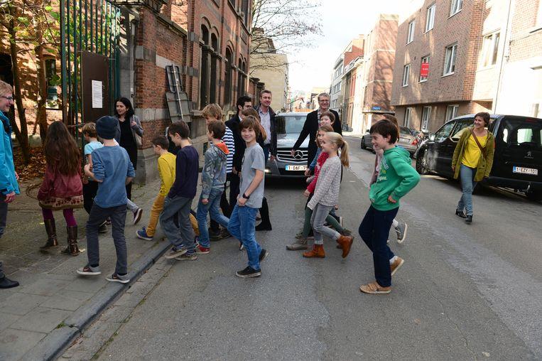 Schepenen Dirk Robbeets en Mohamed Ridouani met de leerlingen van de Appeltuin op straat voor de school.