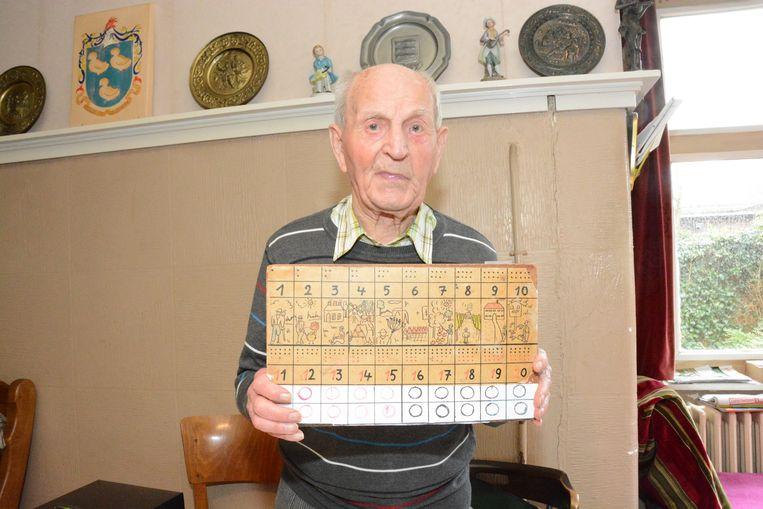 Meester Merckx met een hulpmiddel dat hij creëerde om jongeren spelenderwijs te leren rekenen.