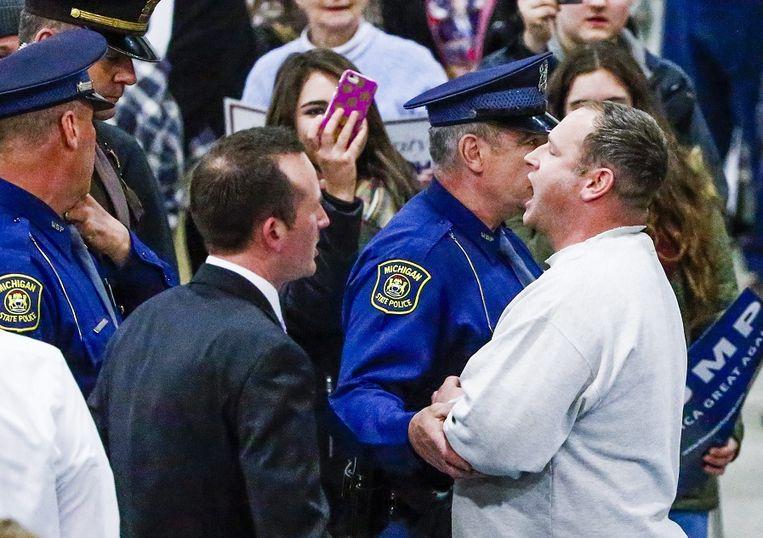Een demonstrant wordt naar buiten geleid bij een toespraak van Donald Trump in Cadillac, Michigan. Beeld epa