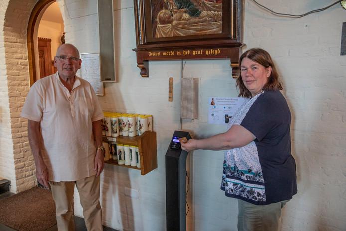 Pastoor Frank As en Kitty Tholen van het parochiebestuur bij de betaalzuil in de Veldhovense Christus Koningkerk.