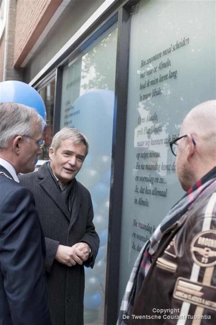 Burgemeester Arjen Gerritsen (links), Herman Finkers en schilder Freddy Hoevers (rechts) bekijken het nieuwe raamgedicht.