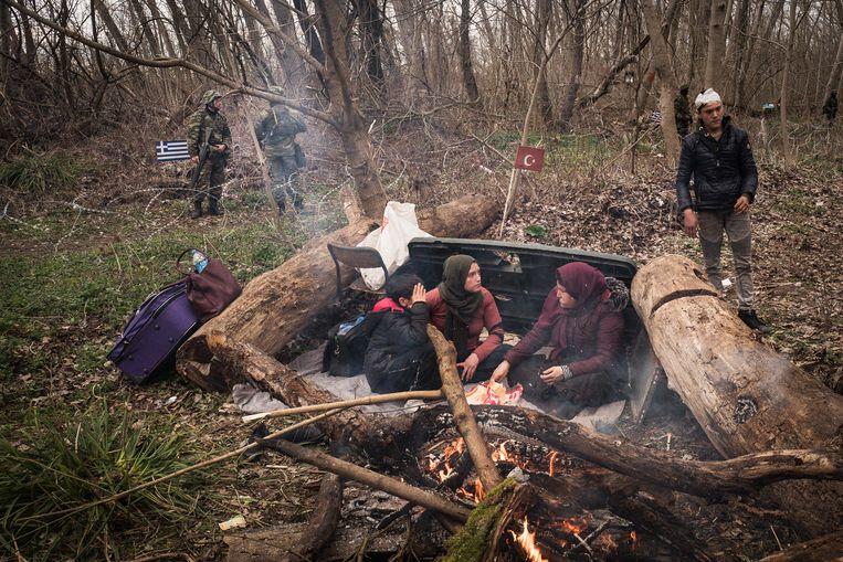 Vluchtelingen stoken een vuurtje in een bos in het niemandsland tussen de Turkse en Griekse grens. Enkele militairen kijken toe. Beeld Zolin Nicola