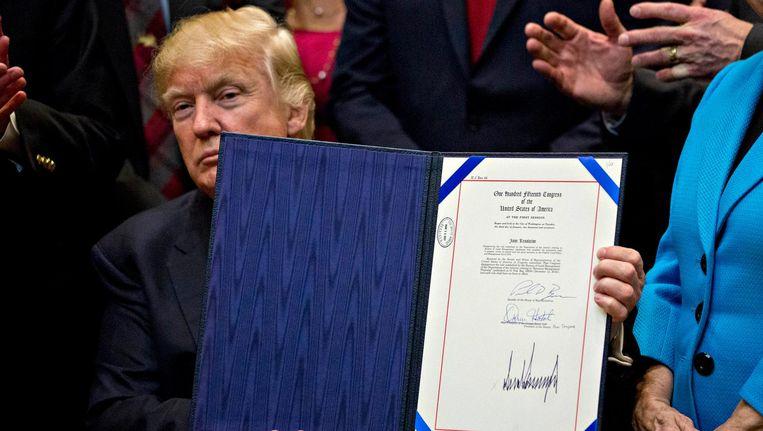 Trump bij de ondertekening van een eerder decreet. Beeld EPA