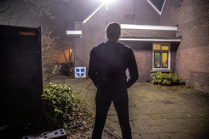 Een buurtbewoner bekijkt de plek waar de politie even eerder forensisch onderzoek deed in de zaak naar de doodgeschoten Henk W.