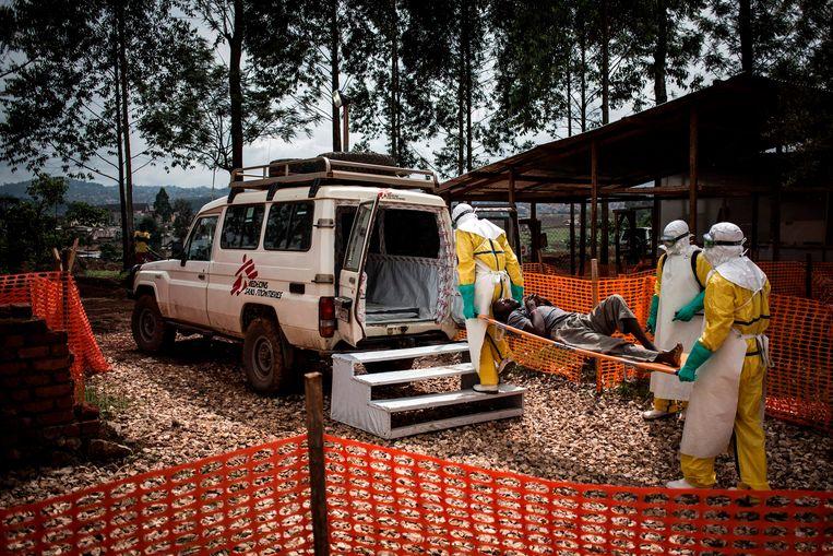 Een ebola-team brengt een zieke naar een ziekenhuis in Congo. Beeld AFP/  John WESSELS