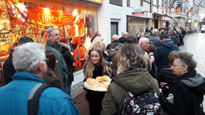 Een medewerkster van Mousset deelt broodjes uit aan de wachtenden voor 'brokkendag'  bij de chocolaterie in de Koningstraat. Verderop loopt een collega met koffie rond.
