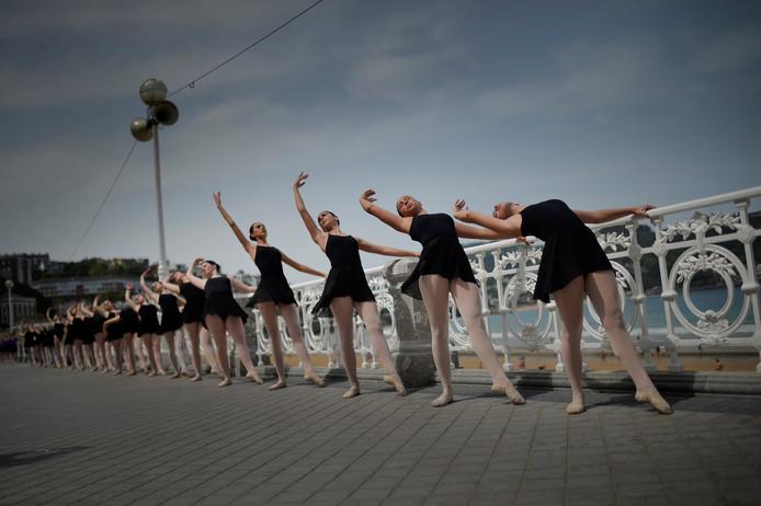 Spaanse balletdansers doen een warming up aan de barre, buiten op de boulevard, langs de Concha baai in San Sebastian. Foto Vincent West
