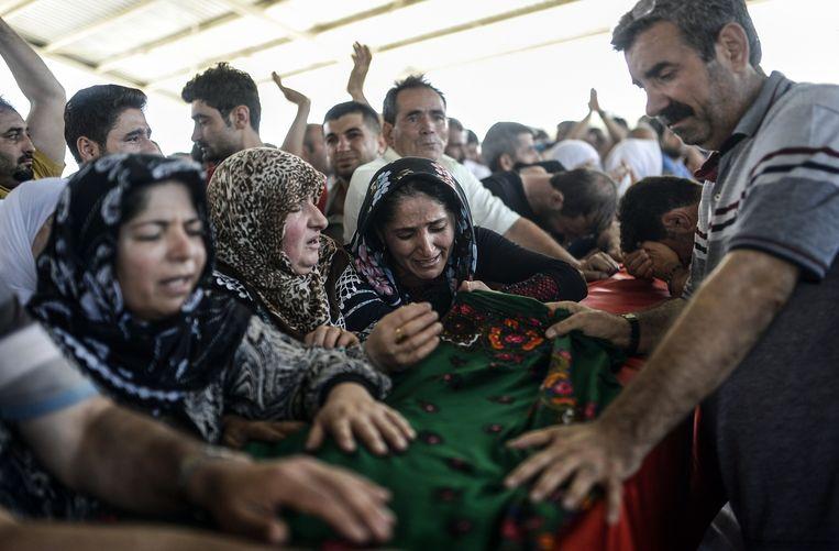Nabestaanden rouwen bij de lichamen van slachtoffers van de zelfmoordaanslag in Suruç. Beeld afp
