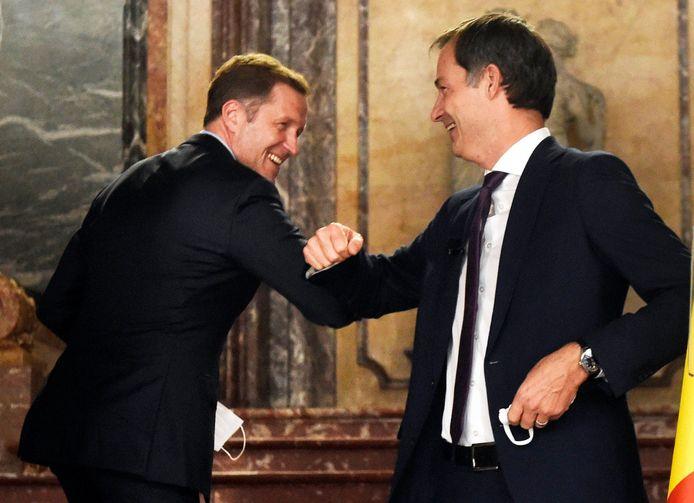 Paul Magnette (PS) en Alexander De Croo (Open Vld) bezegelen het regeerakkoord met een elleboogje. Want een handdruk is niet coronaproof,  al zou je zweren dat de twee elkaar na zo'n onderhandelings-marathon als nauwe contacten mogen beschouwen.