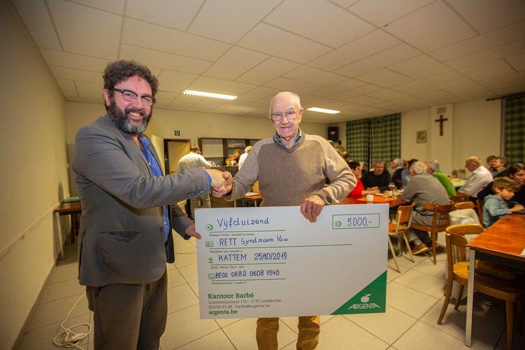 Jean Van der Plas, oudste lid van Team Kattem, schonk de symbolische cheque aan acteur Luc Nuyens.
