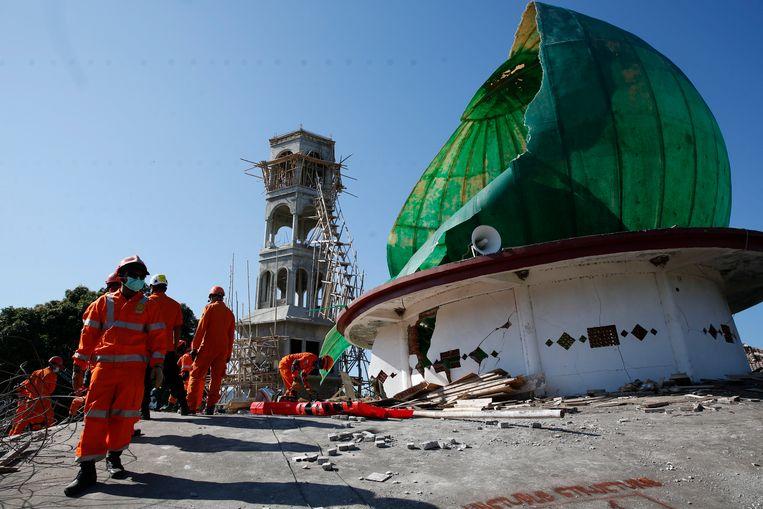 Hulpverleners zoeken naar overlevenden na de verwoestende aardbeving van zondag op het Indonesische eiland Lombok.     Beeld null