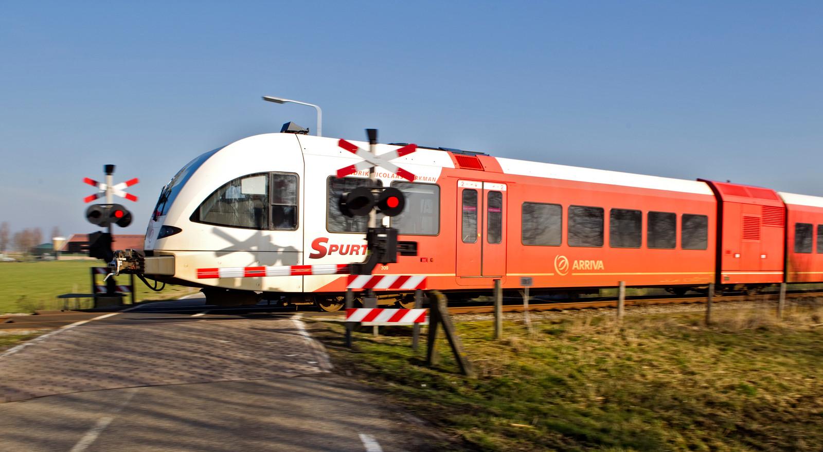 Een trein van Arriva rijdt over een enkel spoor tussen Sneek en Stavoren door het Friese platteland.