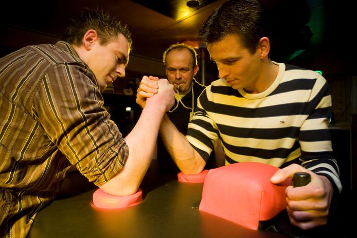 Beeld van een eerder gehouden Albergse kampioenschappen armworstelen, arbiter Henny Paus (midden) houdt de deelnemers in de gaten.