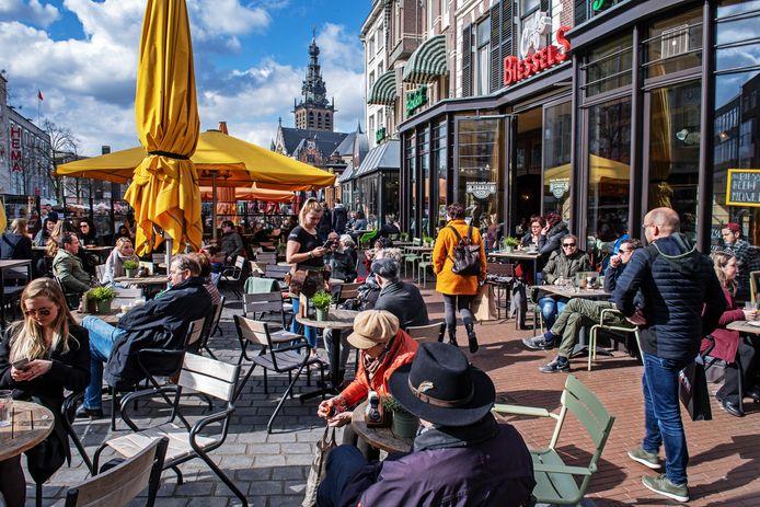 In het zonnetje op het terras op de Grote Markt in Nijmegen, daags voor alle horeca dicht moet.