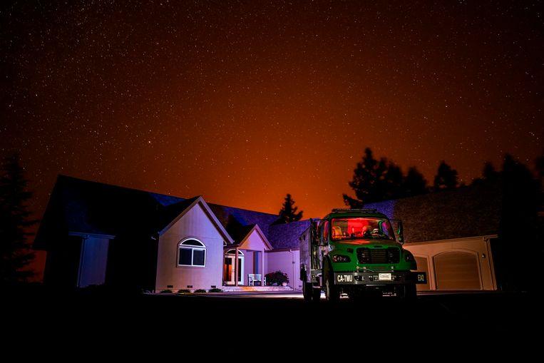 Terwijl een van de Californische bosbranden de nacht verlicht, staat een wagen van de US Forest Service geparkeerd voor een huis in Knights Valley. De branden in de Amerikaanse staat zijn zo hevig dat de noodtoestand is uitgeroepen. Honderdduizenden mensen moesten hun woning ontvluchten.  Beeld AFP