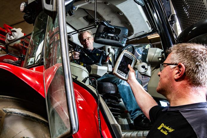 Peter Bruggeman (r) en Gerrit Boschloo (in tractor) laten het nieuwe GPS-systeem.