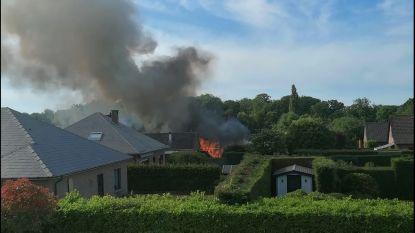 Brandend tuinhuis en haag zorgen voor rookpluim
