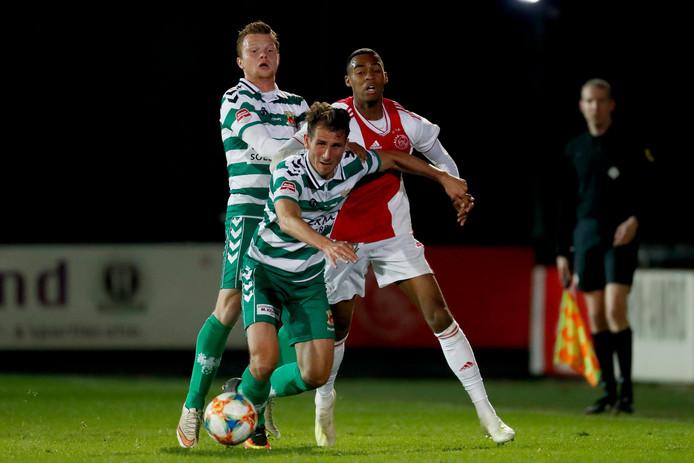 Paco van Moorsel van Go Ahead Eagles probeert zich Ryan Gravenberch (Jong Ajax) van het lijf te houden.