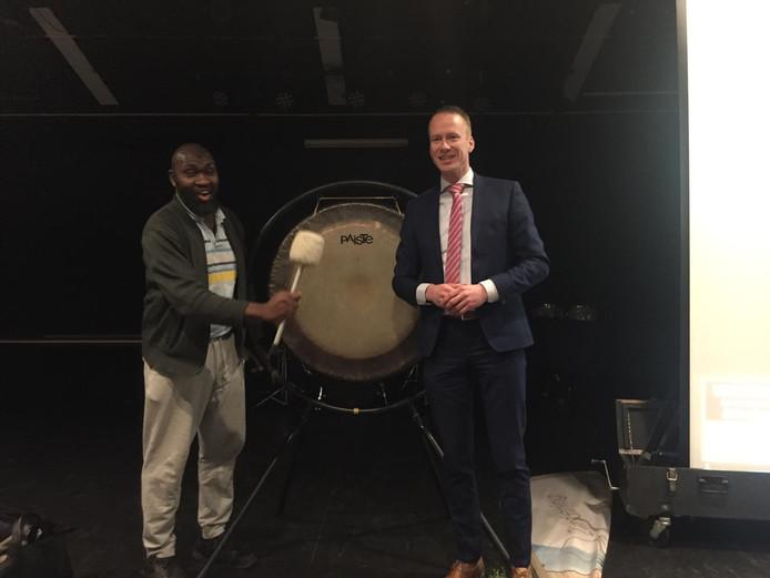 Musa Mawanda en wethouder Cees van den Bos openen de Vacaturemarkt Renesse met een klap op de gong. Mawanda doorliep met succes een integratieproject en werkt nu bij een groot installatiebedrijf op het eiland