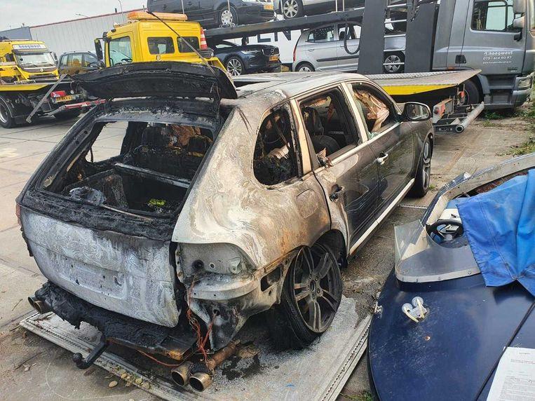 De afgebrande en  inmiddels weggesleepte Porsche Cayenne. Beeld Het Parool